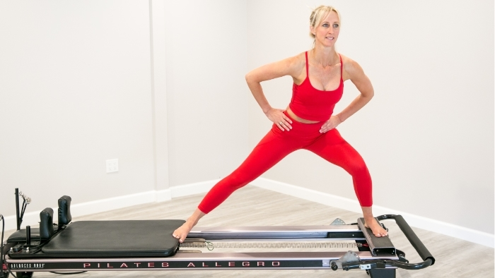 women in red workout outfit standing on pilates reformer